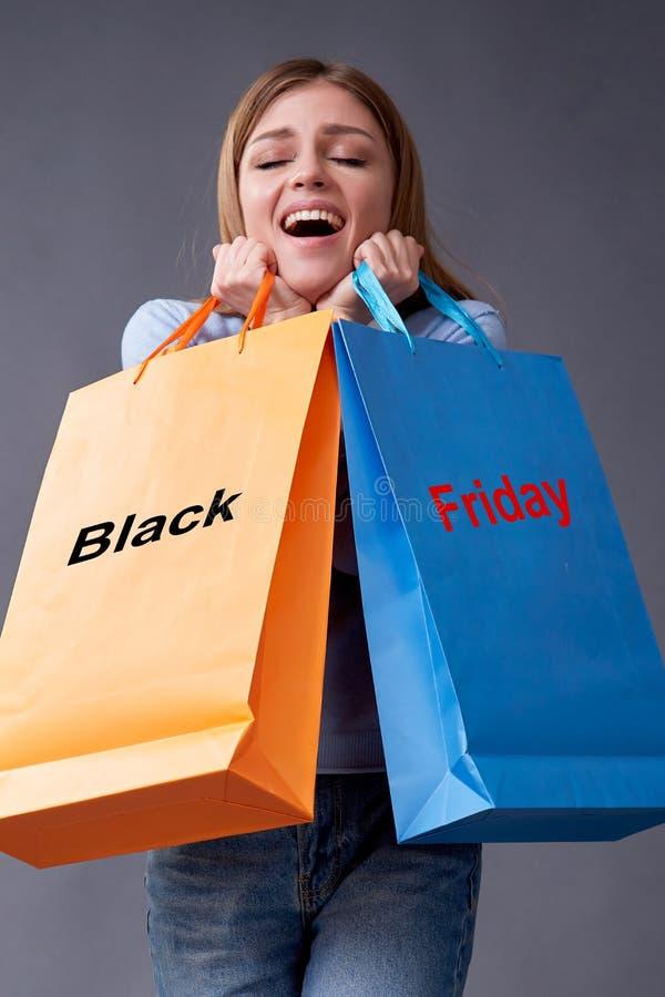 Svart fredag, konceptet Shopping and commerce Spara och rabatt Kvinnor med påsar som står på grå bakgrund arkivfoton