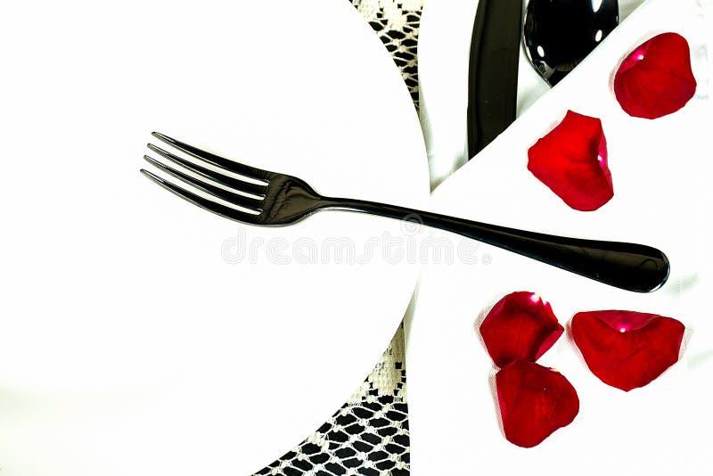 Svart gaffel med rosa kronblad arkivfoton