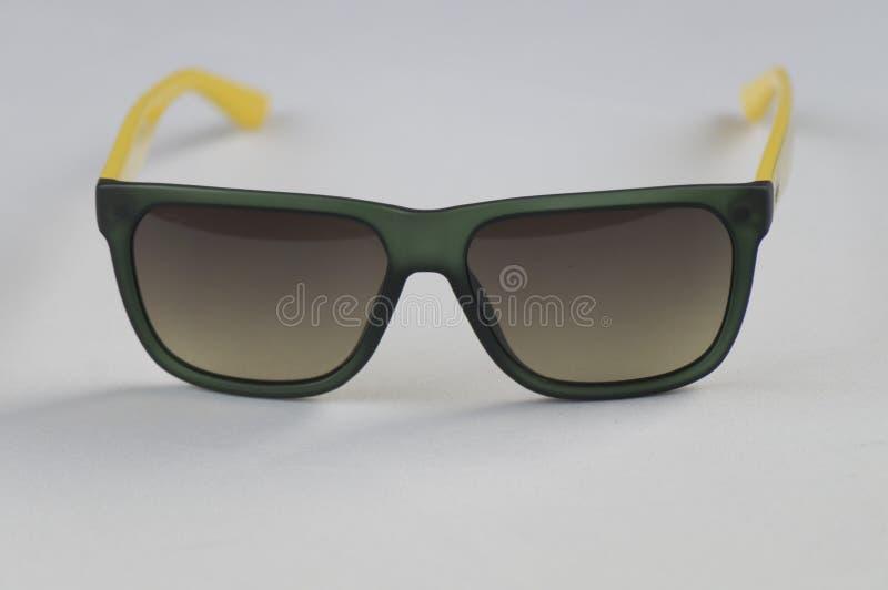 svart glasad solglasögon med det gula handtaget som förläggas på vit bakgrund royaltyfri foto