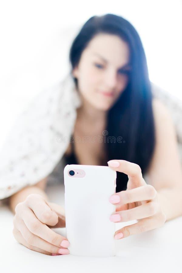 Svart haired sexig kvinna som kopplar av och använder mobiltelefonen på säng som selfiefunktionsläge arkivbilder