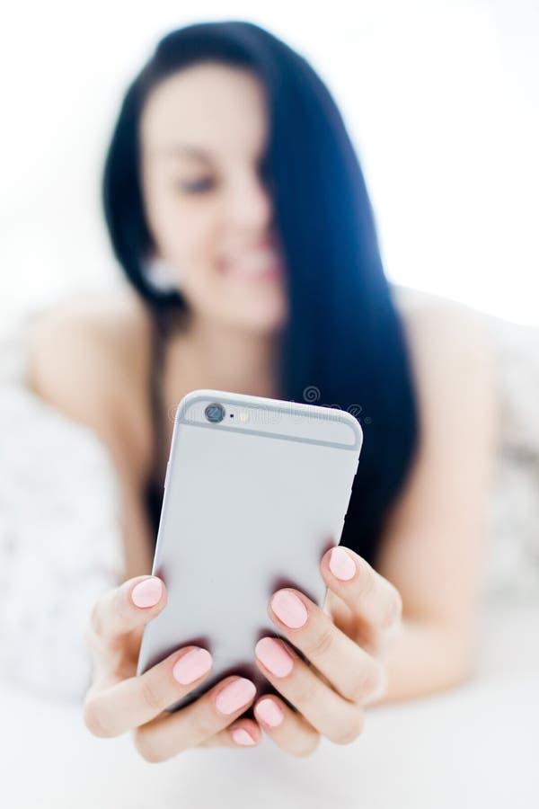 Svart haired sexig kvinna som kopplar av och använder silvermobiltelefonen på säng arkivbilder