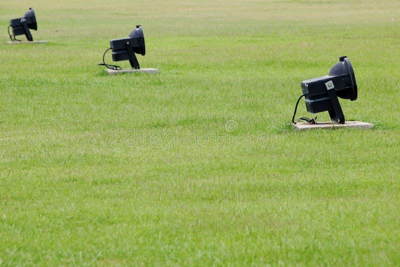 Svart halogenstrålkastare på trädgårdgolv för grönt gräs arkivbilder