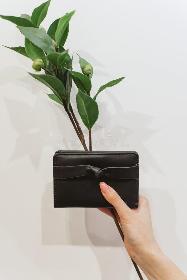 Svart handväska och filial med blommor royaltyfria bilder