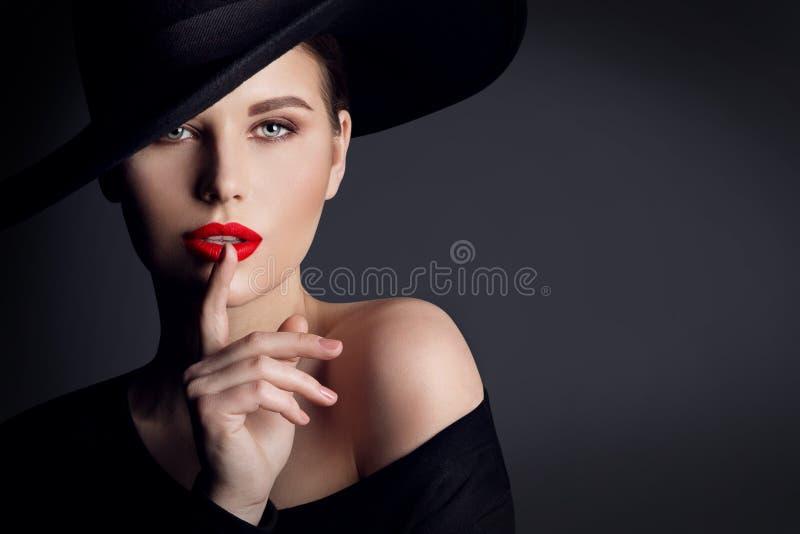 Svart hatt för kvinna, elegant modemodell Beauty Portrait, finger på tyst gest för kanter royaltyfri fotografi