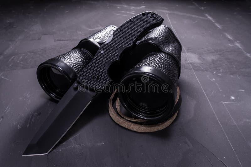 Svart hopfällbar kniv och svart kikare Vapen och optik arkivbilder