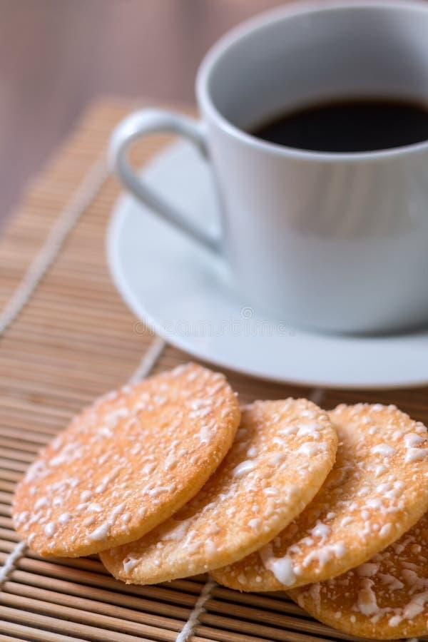 Svart kaffe i den vita koppen och frasiga rissmällare med på woode royaltyfri bild