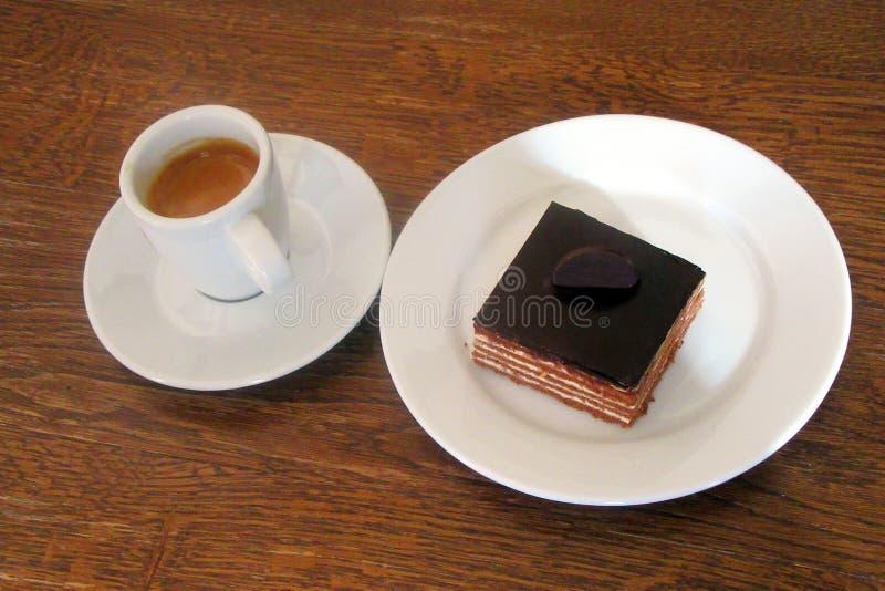 Svart kaffe i en kopp och bredvid det är en ostkaka royaltyfria bilder