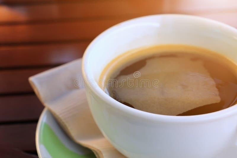 Svart kaffe i koppvit på bakgrund för tabellträgolv i morgon arkivfoto