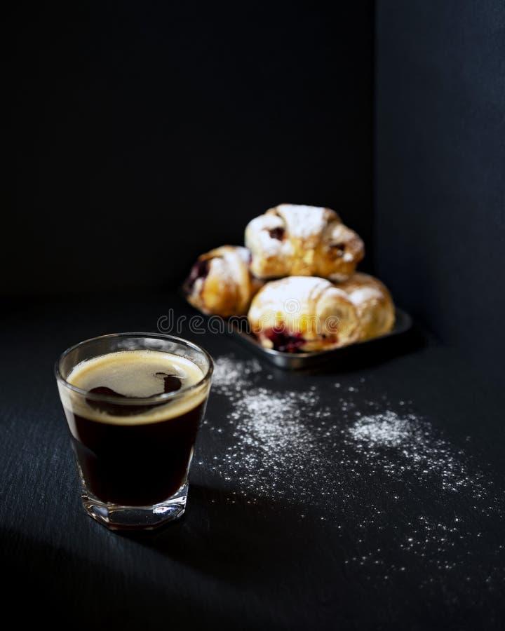 Svart kaffe med baglar arkivfoto