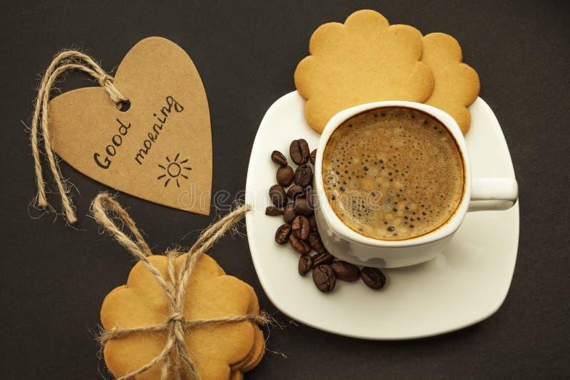 Svart kaffe med kaffebönor och kakor på en mörk bakgrund Frukost bästa sikt fotografering för bildbyråer