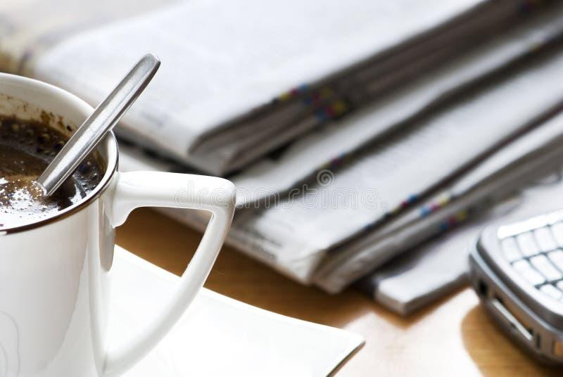 Svart kaffe och en tidning royaltyfria foton