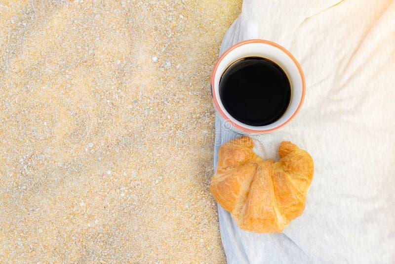 Svart kaffe och giffel på sandbakgrund, frukost på det strand-, mat- och drinkbegreppet royaltyfri foto