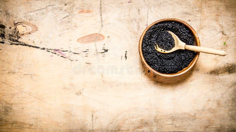 Svart kaviar i en bunke med en träsked royaltyfri bild