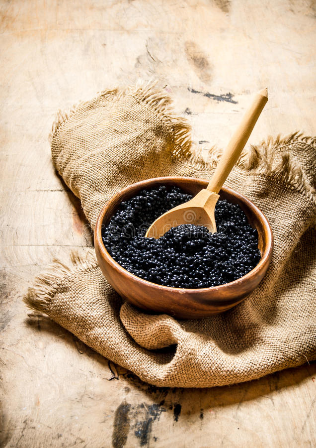 Svart kaviar i träbunke på gammalt tyg trägrund tabell för djupfält arkivbild
