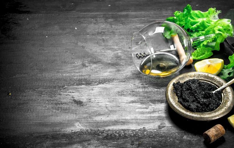 Svart kaviar med vitt vin och örter royaltyfri foto