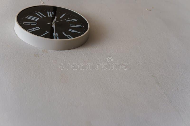 Svart klocka som hänger på den vita väggen royaltyfria foton
