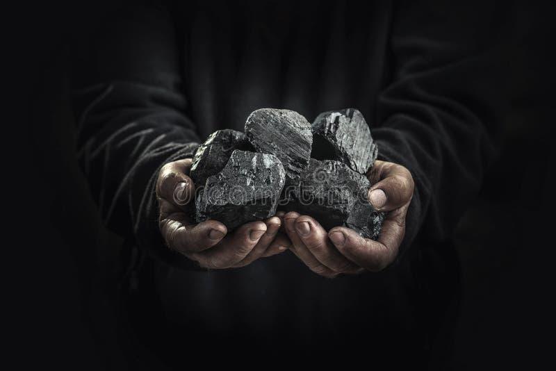 Svart kol i händerna, tung bransch, uppvärmning royaltyfri foto