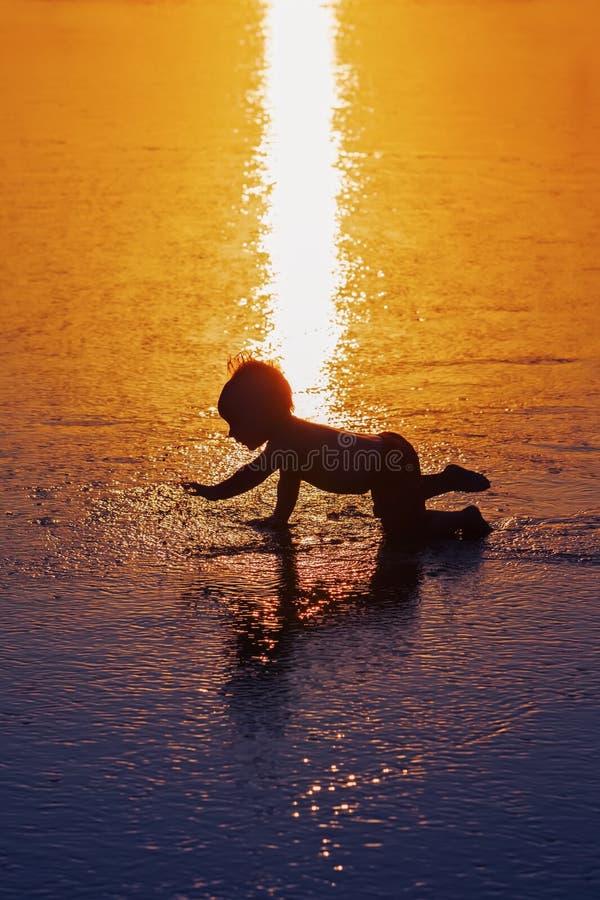 Svart kontur av det lilla barnet på den våta solnedgångstranden fotografering för bildbyråer