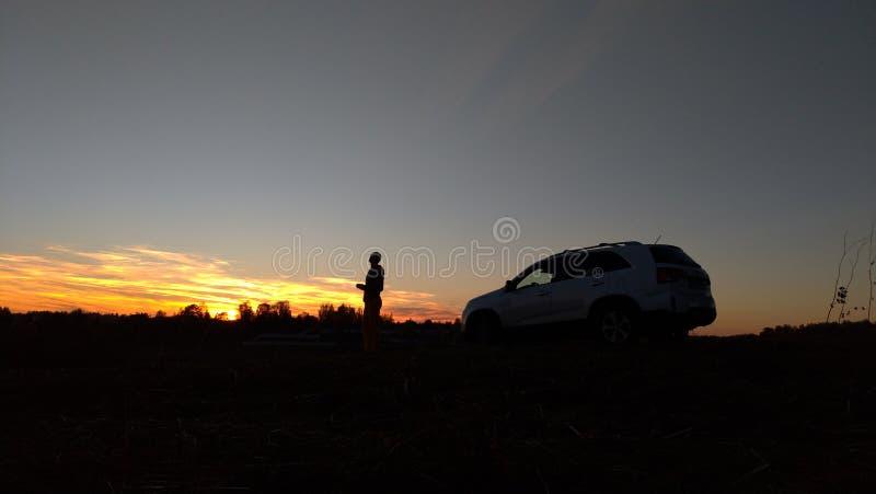 Svart kontur av en växt, en man och en bil på bakgrunden av en solnedgång och en blå himmel royaltyfria foton