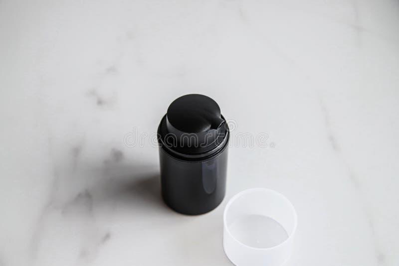 Svart kosmetisk flaska på ljusmarmorbakgrund royaltyfria foton