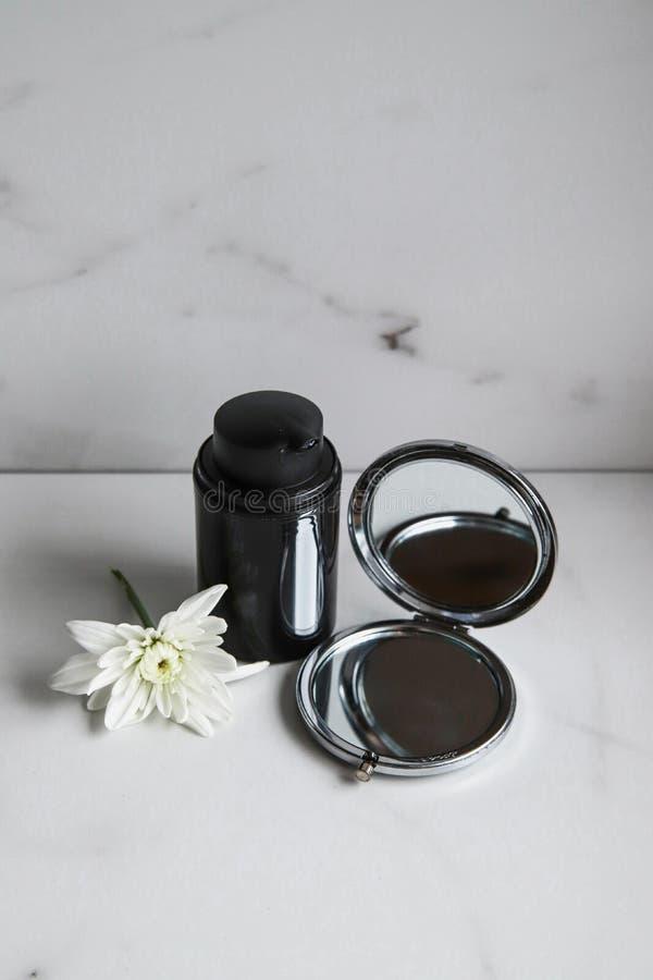 Svart kosmetisk flaska, spegel och vit blomma på ljusmarmorbakgrund arkivbild