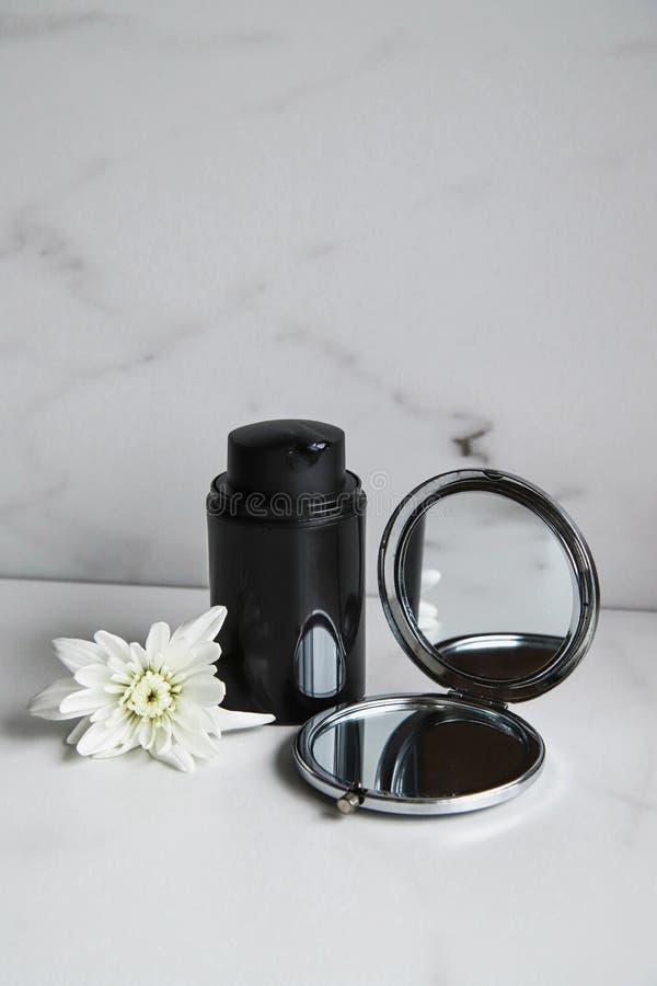 Svart kosmetisk flaska, spegel och vit blomma på ljusmarmorbakgrund royaltyfri fotografi