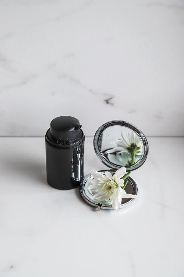 Svart kosmetisk flaska, spegel och vit blomma på ljusmarmorbakgrund arkivfoto