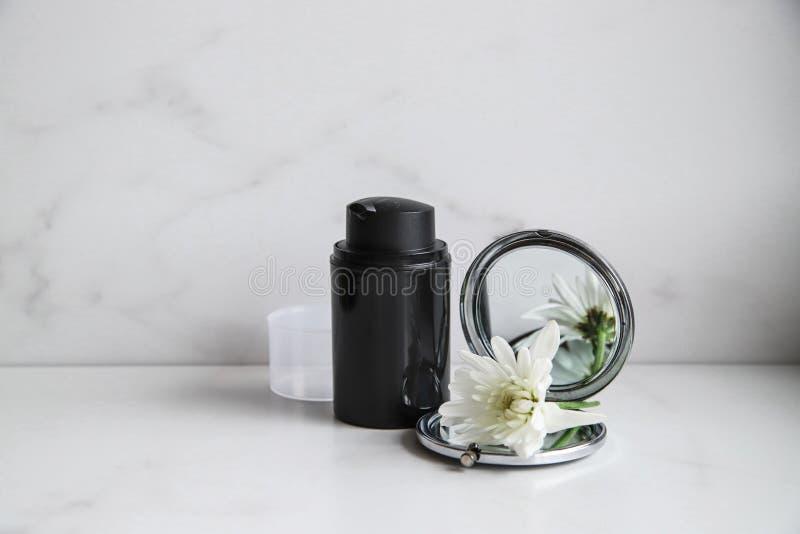Svart kosmetisk flaska, spegel och vit blomma på ljusmarmorbakgrund fotografering för bildbyråer