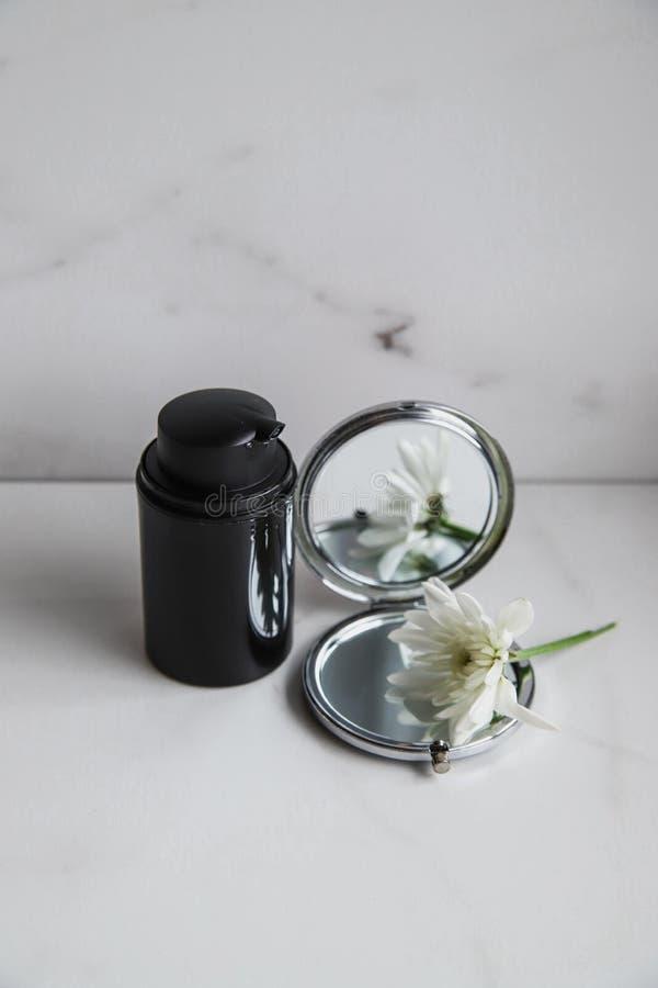 Svart kosmetisk flaska, spegel och vit blomma på ljusmarmorbakgrund royaltyfri foto