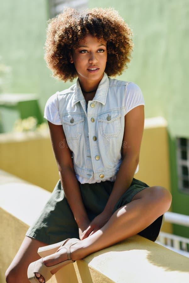 Svart kvinna afro frisyr, bärande tillfällig kläder i stads- bac royaltyfri bild