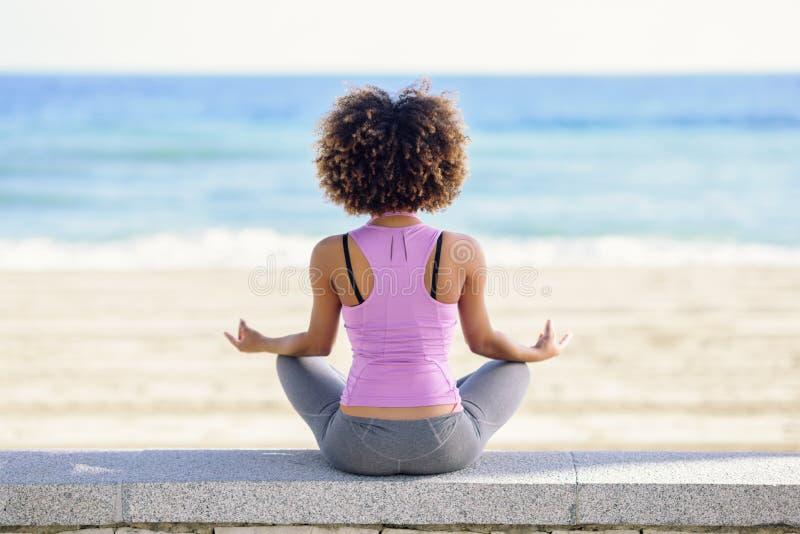 Svart kvinna afro frisyr som gör yoga i stranden fotografering för bildbyråer