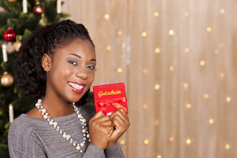 Svart kvinna framme av julträdet royaltyfria foton