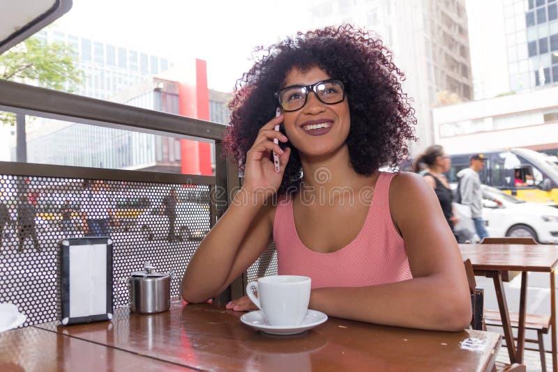 Svart kvinna med burrigt hår genom att använda mobiltelefonen utomhus och havin royaltyfri bild
