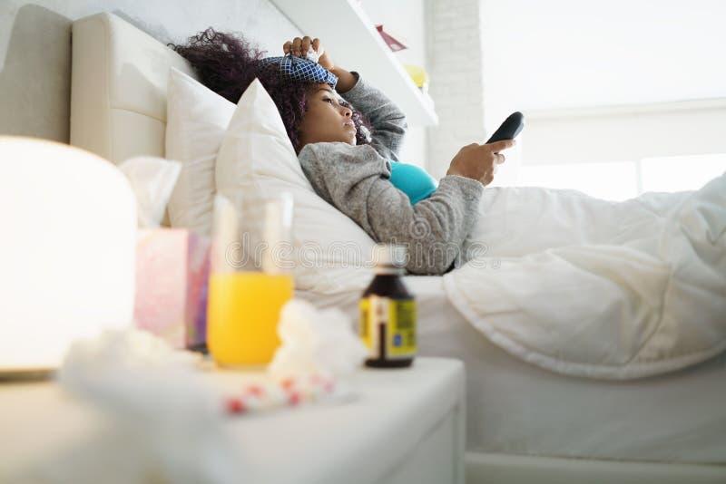 Svart kvinna med influensa och hållande ögonen på tv för förkylning hemma royaltyfri foto