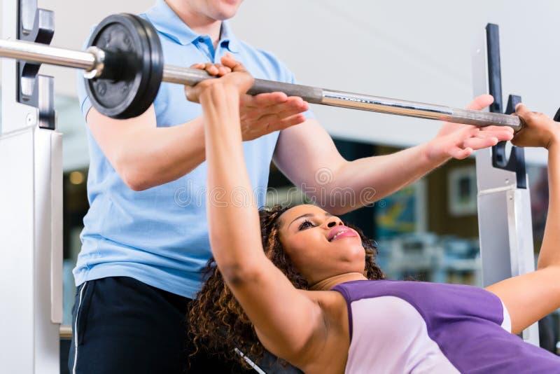 Svart kvinna med instruktörlyftande vikter i idrottshallen för kondition royaltyfri foto