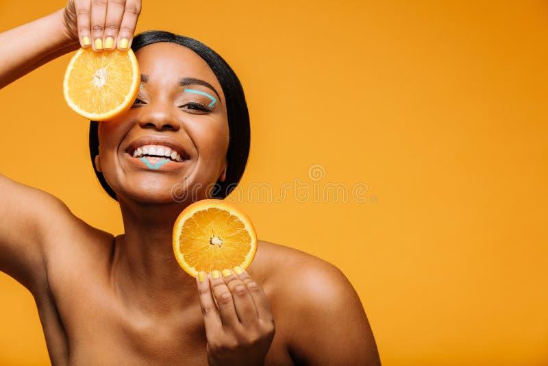 Svart kvinna med sunda hud- och apelsinskivor royaltyfria foton
