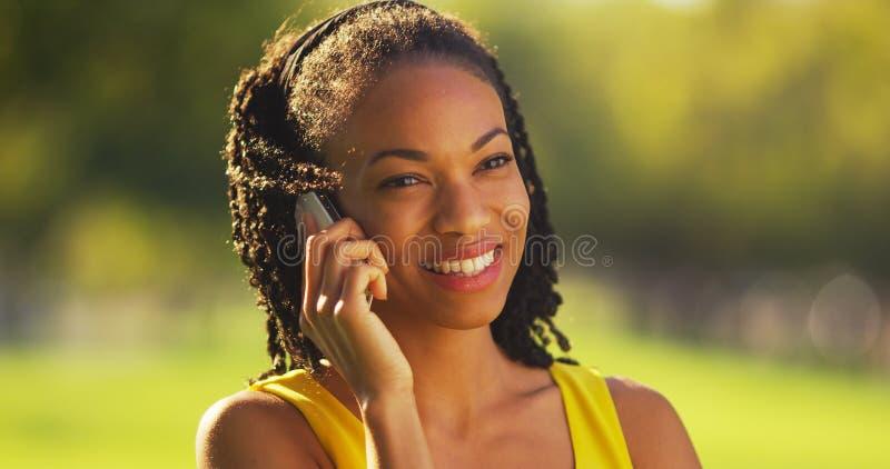 Svart kvinna på telefonen som utomhus skrattar arkivfoto