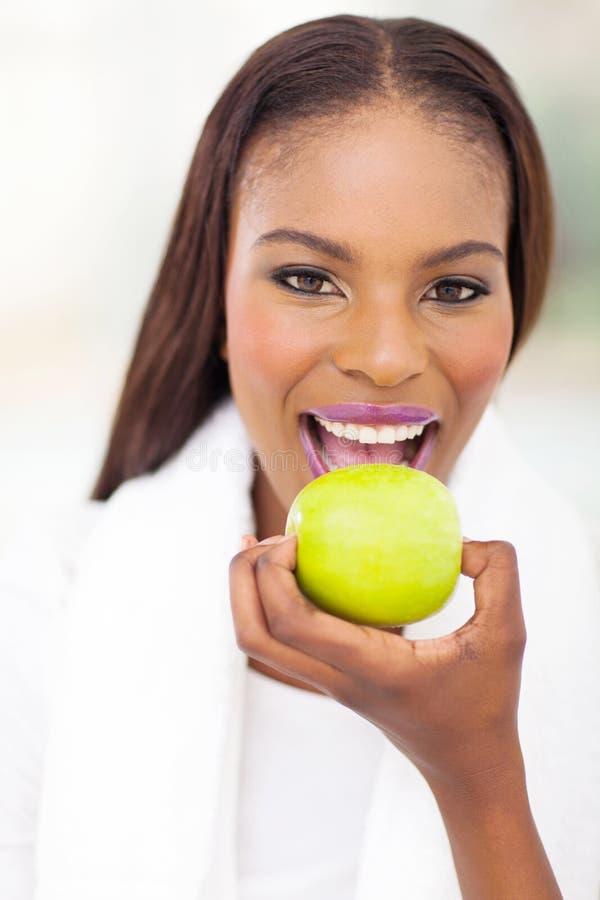 Svart kvinna som äter äpplet arkivfoto