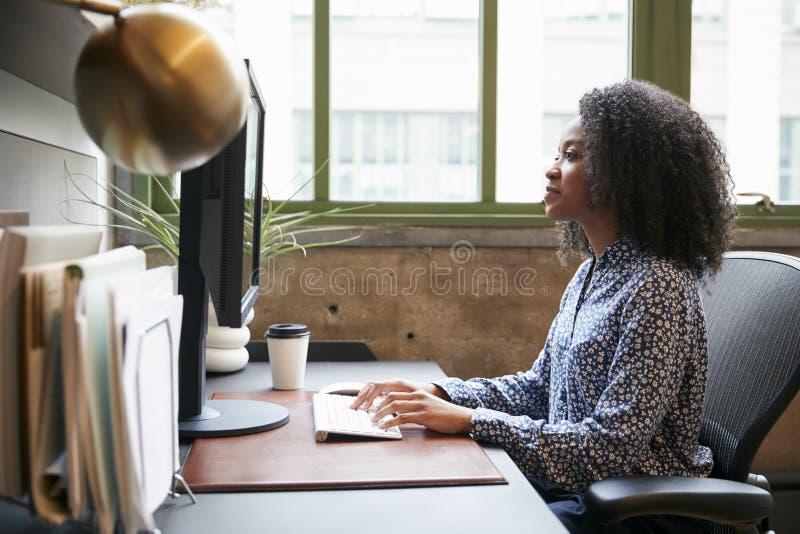 Svart kvinna som arbetar på en dator i ett kontor, sidosikt arkivbilder