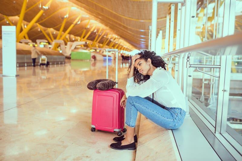 Svart kvinna som förargas och frustreras på flygplatsen med flygcanc arkivbild