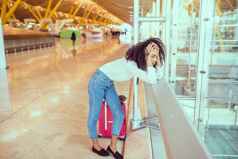 Svart kvinna som förargas och frustreras på flygplatsen med flygcanc royaltyfria bilder