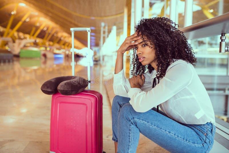Svart kvinna som förargas och frustreras på flygplatsen med flygcanc arkivfoto