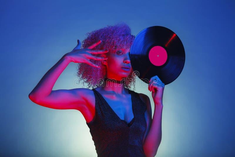 Svart kvinna som rymmer en retro vinyl med eightiesdiskomusik royaltyfri fotografi