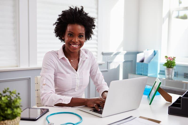 Svart kvinnlig doktor på arbete i ett kontor som ser till kameran arkivbild