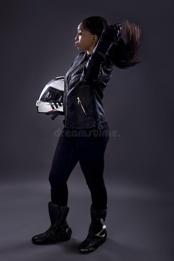Svart kvinnlig racerbil som fixar hennes hår royaltyfri foto