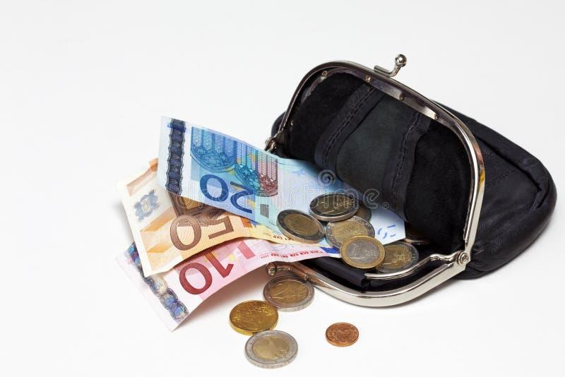 Svart läderhandväska med euroanmärkningar och mynt på vit bakgrund arkivbild