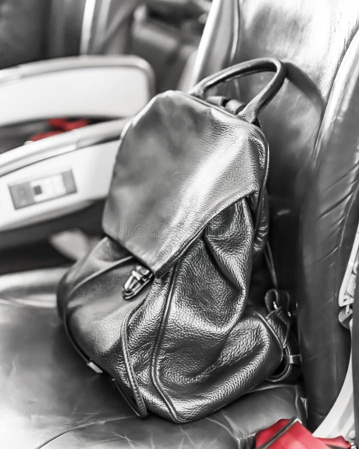 Svart läderryggsäck på platsen ombord flygplanet Handbagagebagage royaltyfri bild