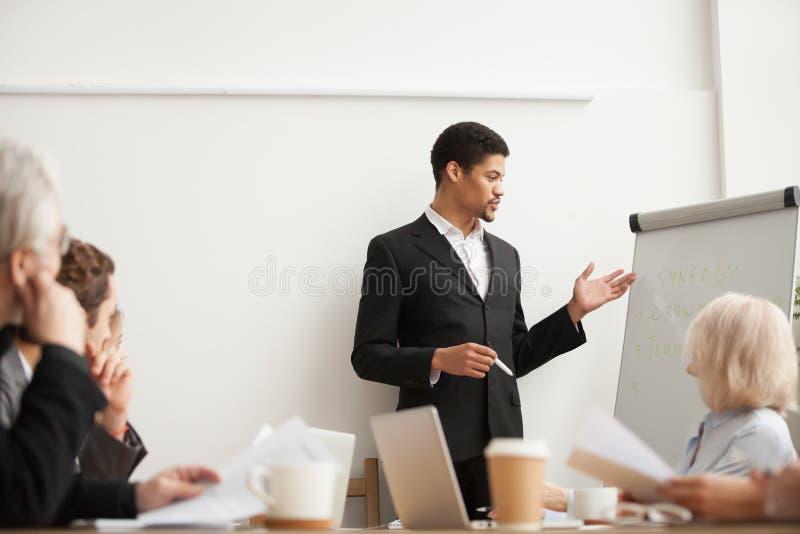 Svart lagledare som ger presentation till anställda på konferensgruppen royaltyfri foto