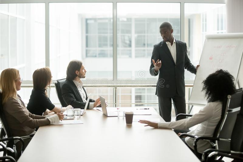 Svart lagledare som ger presentation till klienter på konferensmötet fotografering för bildbyråer