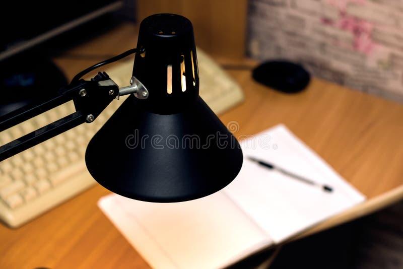 Svart lampa ovanför tabellen med anteckningsboken, tangentbordet och musen royaltyfri fotografi